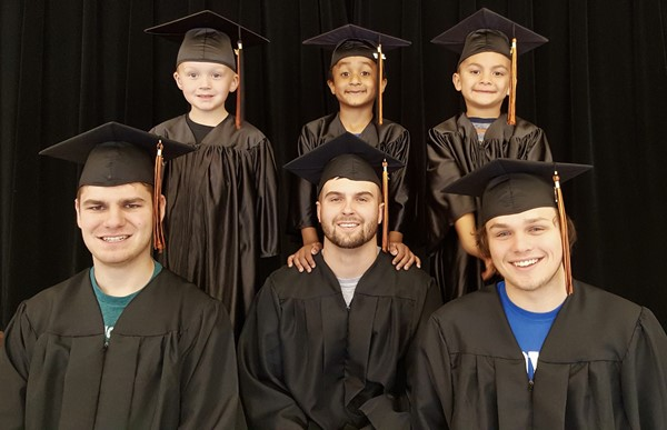 A few senior boys and kindergarten graduates in their caps and gowns.
