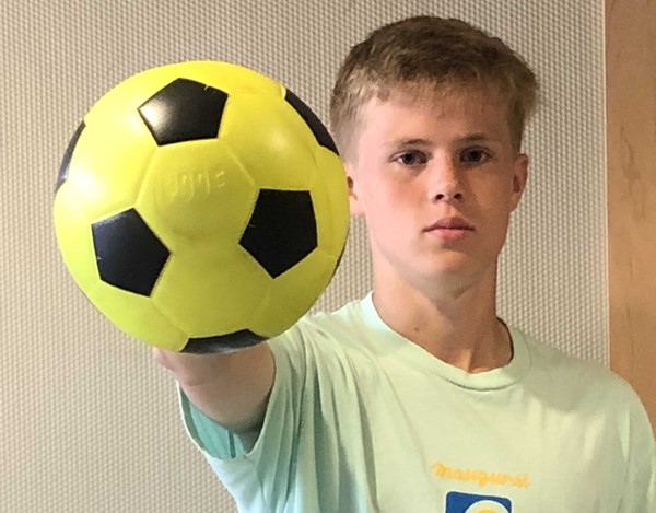 student with soccer ball