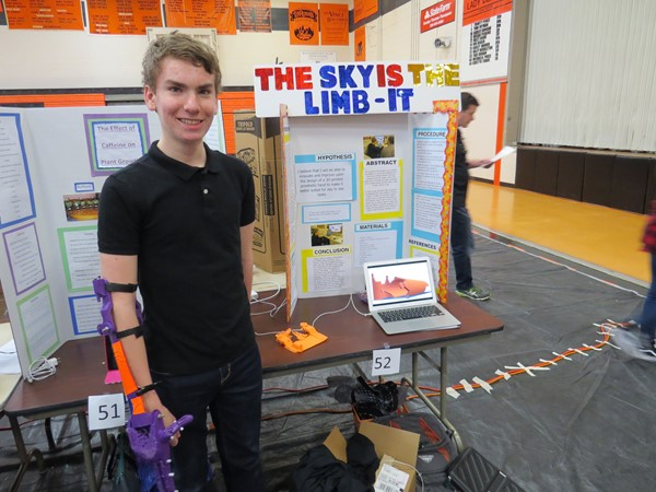An 8th grade student displays his science fair project; a 3D printed prosthetic arm