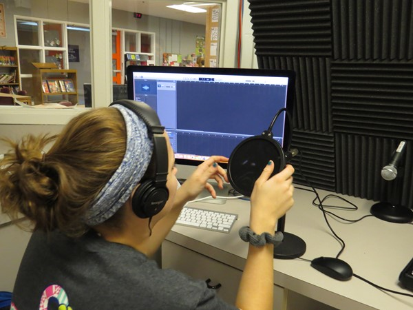Student recording a podcast for an assignment using Garage Band