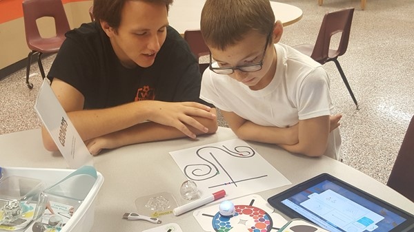 a senior helping an elementary student learn the ways of the ozobot
