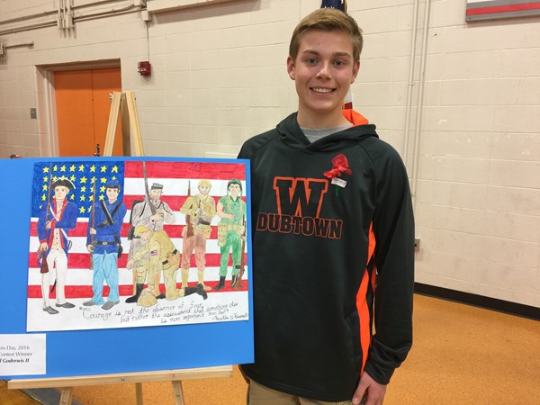 an 8th grade student with award winning his Veteran's Day poster